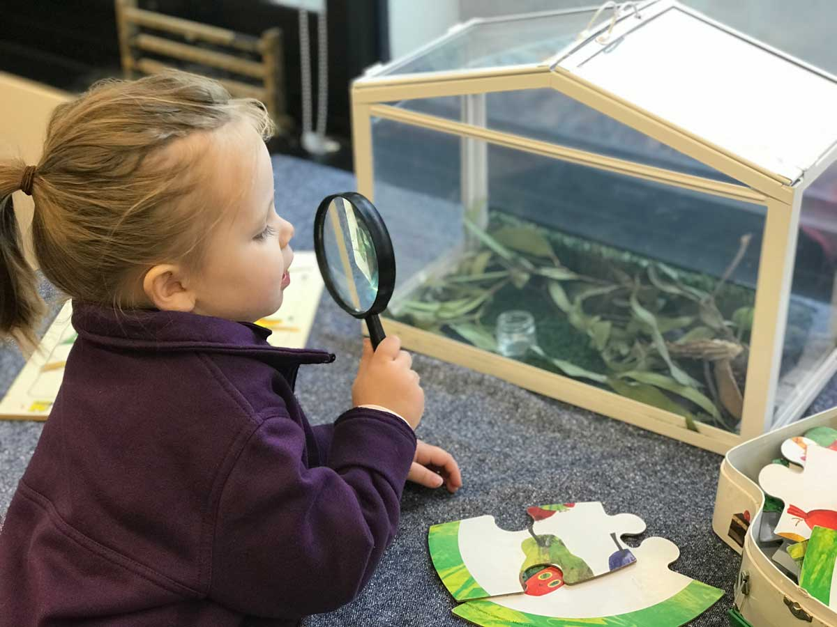 Zara, an ECLC student, uses a magnifying glass to look at casemoths