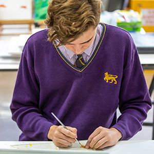 A Senior male student painting a canvas