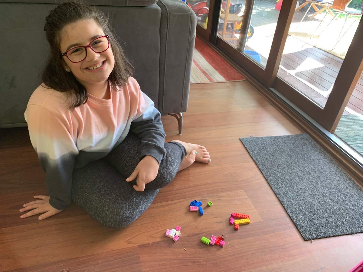 Maya Portelli sitting with Lego blocks around her on the floor