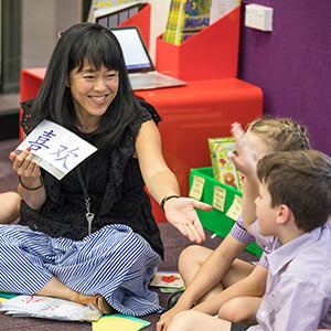 Teacher holding a card with a Chinese symbol on it motioning towards a child with his hand raised