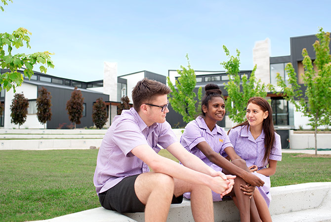 Students sitting together outside boarding facilities