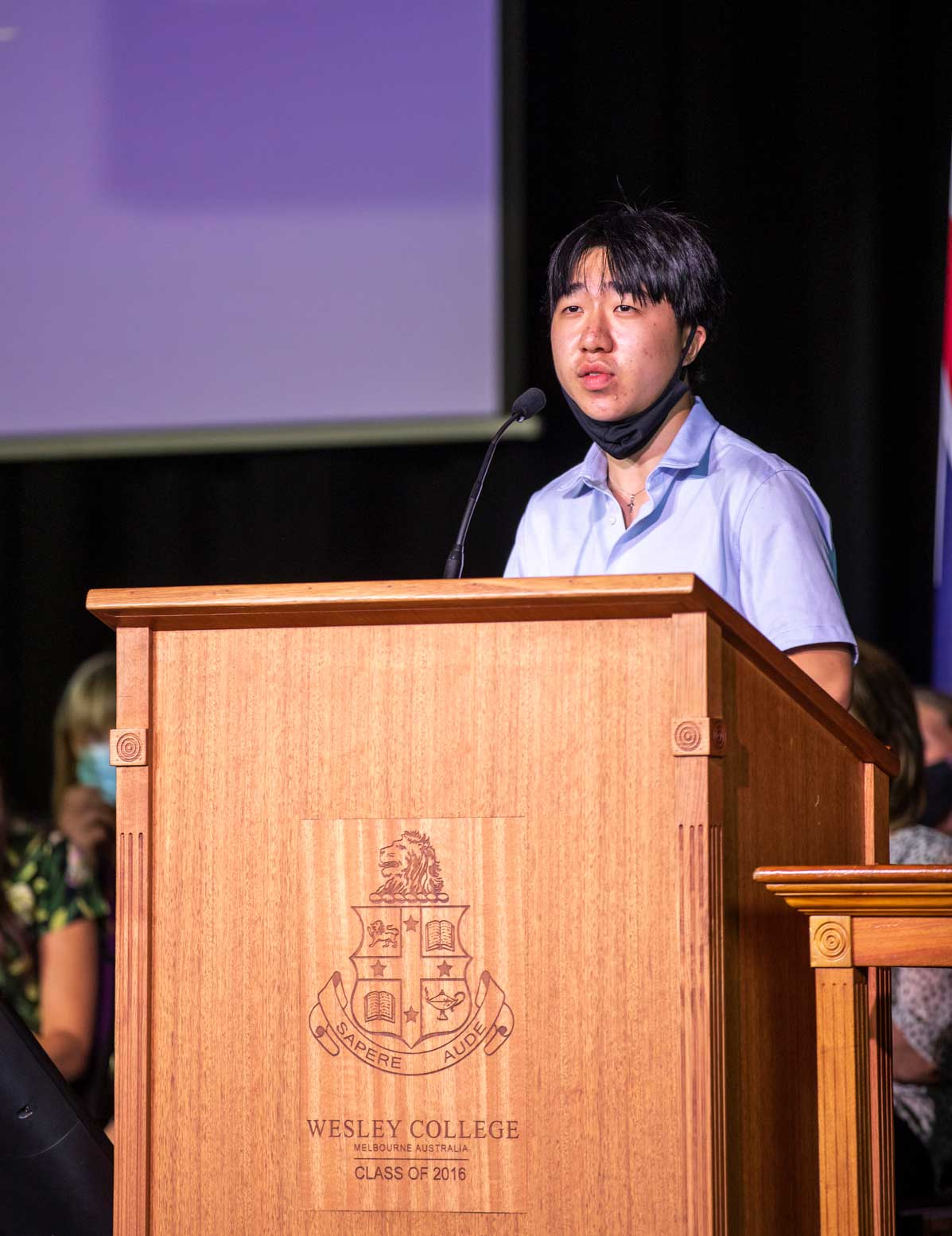 Kean Tan stands at the lectern giving the Scholar's Address at assembly
