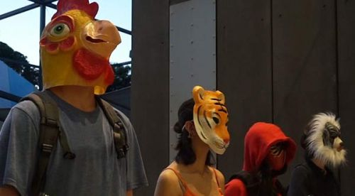 Student actors in a film wearing animal masks and holding plastic guns