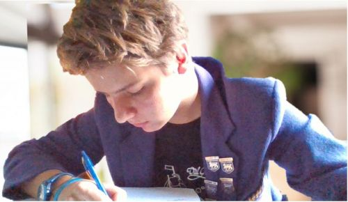 Boy studying while wearing a purple blazer, from a previous iteration of the Wesley uniform