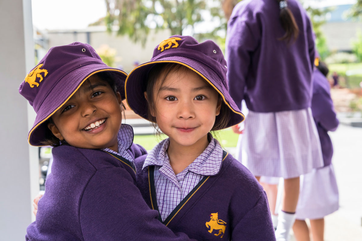 Two Junior School children smiling in their Wesley hats